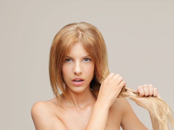 Blonde woman holding dry hair